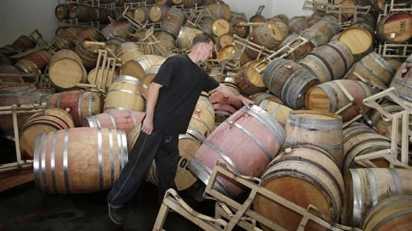 Cellar worker Daniel Nelson looks over toppled barrels of cabernet sauvignon following an earthquake at the B.R. Cohn Winery barrel storage facility in Napa, Calif. Winemakers in California's storied Napa Valley woke up to thousands of broken bottles, barrels and gallons of ruined wine as a result of Sunday's earthquake.