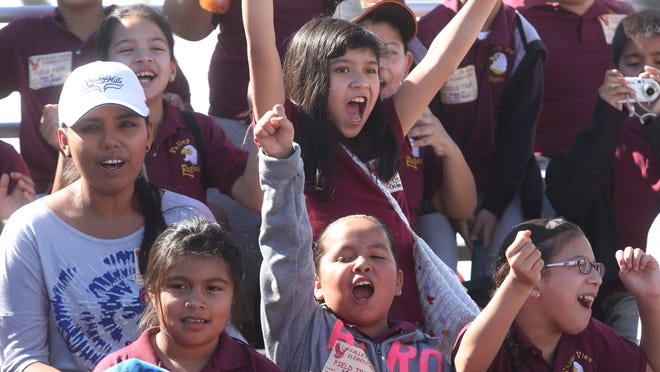 Kids cheer on the first pig race Friday.