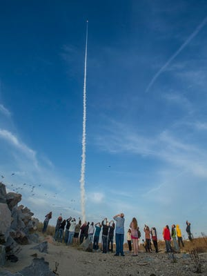 In this file image, university students and instructors participating in RockSat-X look on as the NASA Terrier-Improved Malemute sounding rocket heads to the sky carrying their experiments in this file image.