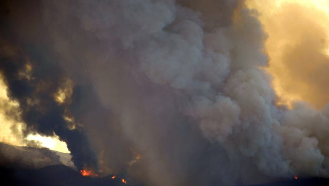 Flames erupt on the hills above Pleasants Valley Road, Tuesday, July 28, 2015, near Winters, Calif. More than 200 people were ordered from their homes Tuesday when the wildfire jumped a containment line east of California's Napa Valley wine country in one of several blazes burning across the state. (Joel Rosenbaum/The Vacaville Reporter via AP)