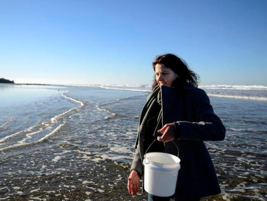 Terry Waldron collects sea water samples that will