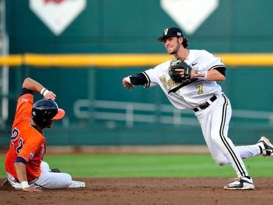 Vanderbilt's Dansby Swanson (7) throws a ball to first after forcing out Virginia's Daniel Pinero at second during the third inning in the last game of the College World Series at TD Ameritrade Park, Wednesday, June 24, 2015, in Omaha, Neb.