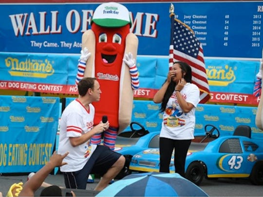 Competitive eater Joey Chestnut proposes to his girlfriend and fellow competitor Neslie Ricasa before the Nathan's Famous Fourth of July International Hot Dog Eating contest at Coney Island, Friday, July 4, 2014, in Brooklyn. Chestnut won his competition and eighth consecutive contest by finishing 61 hot dogs and buns.