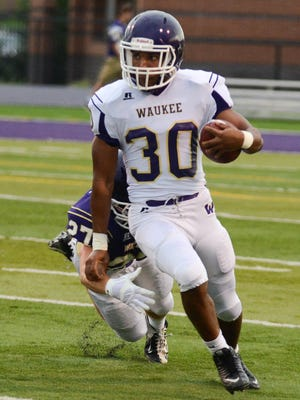 Running back #30 Trevor Allen, 17, a senior, evades a tackle, at the Waukee High School Power Bowl, a tune up Scrimmage held for the Freshmen, Sophomores, and the Varsity football teams the Friday before the first game. Held at Waukee Stadium on Friday, August 22, 2014.