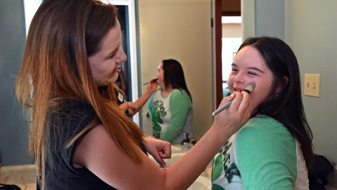 Eilish Kelderman, left, puts makeup on her sister Kailin Kedlerman as they get ready for their graduation from McQueen High School in 2014. Both are now enrolled at the University of Nevada, Reno.