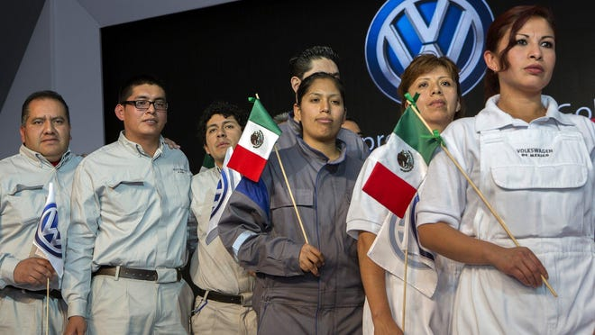 Factory workers attend a Volkswagen AG 50th anniversary event at the company's plant in Puebla, Mexico, on Jan. 14, 2014.