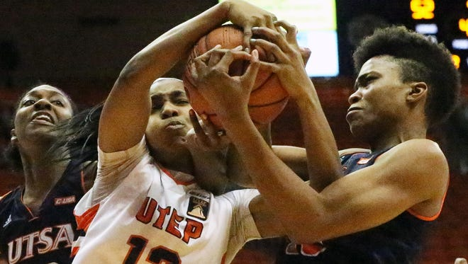 UTEP guard Sparkle Taylor, 12, comes down with an offensive rebound with Tesha Smith of UT-San Antonio Sunday at the Don Haskins Center. At left is Niaga Mitchell-Cole of UTSA. The Miners prevailed 62-55, improving their record to 14-1.