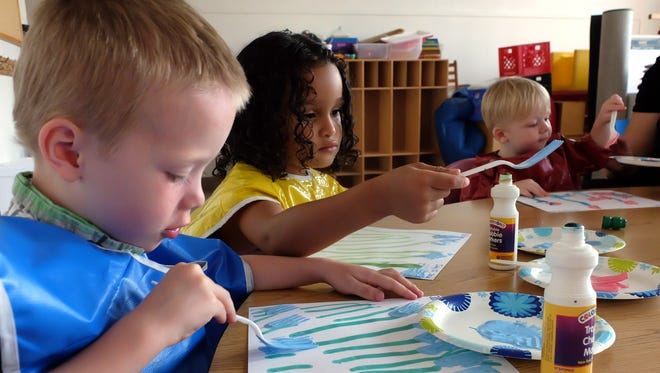 From left, Jarrett Chronister, 4, Edlise Perez, also 4, and Mason Chronister, 1, paint flowers during the child care program at the Community Progress Council for parents getting their GED, Thursday, July 21, 2016. John A. Pavoncello photo