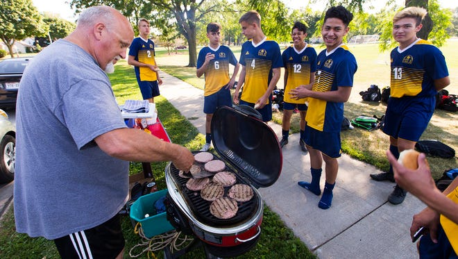 Pius XI  boys soccer coach Hansi Herzog grills burgers for his players before a light practice at Rainbow Park in West Allis. Whenever the team goes three games without being scored upon or a player on his team scores three goals in a match, Herzog grills for the team.