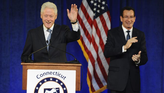 Former President Bill Clinton, left, waves, rally for Gov. Dannel P. Malloy, right, Monday, Oct. 13, 2014, in Hartford, Conn.  (AP Photo/Jessica Hill)
