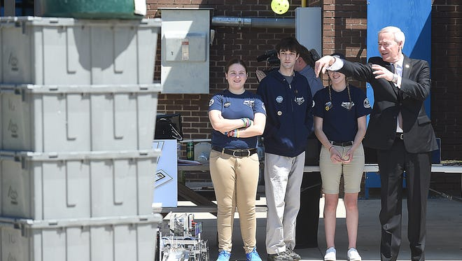 Mountain Home High School Bomb Squad robotics team members look on as Arkansas Gov. Asa Hutchinson tosses a ball Tuesday at a robot built by the team. Hutchinson was at Mountain Home High School promoting his initiative to provide coding classes in every Arkansas high school.