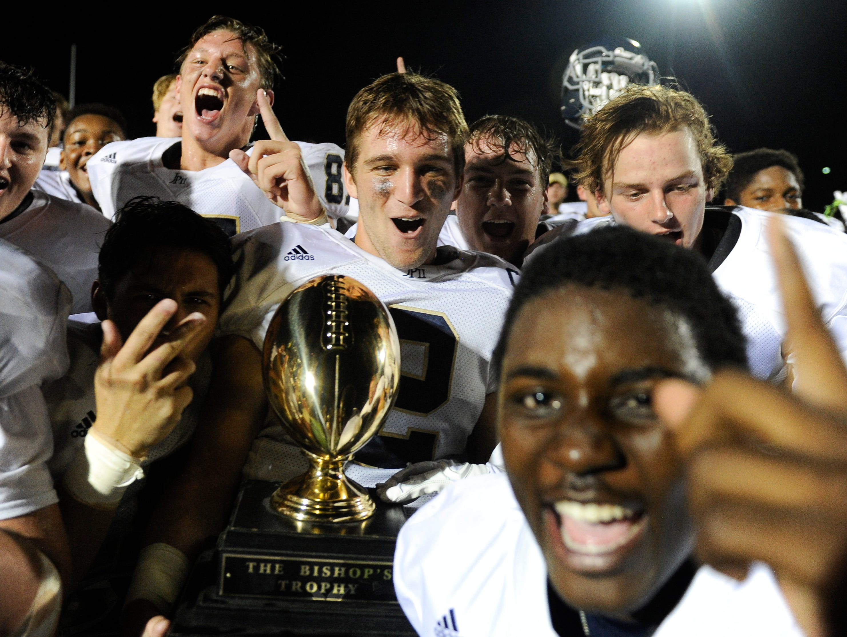Members of the John Paul II football team celebrate their win over Father Ryan with the Bishop's trophy Friday Sept. 9, 2016, in Nashville, Tenn.