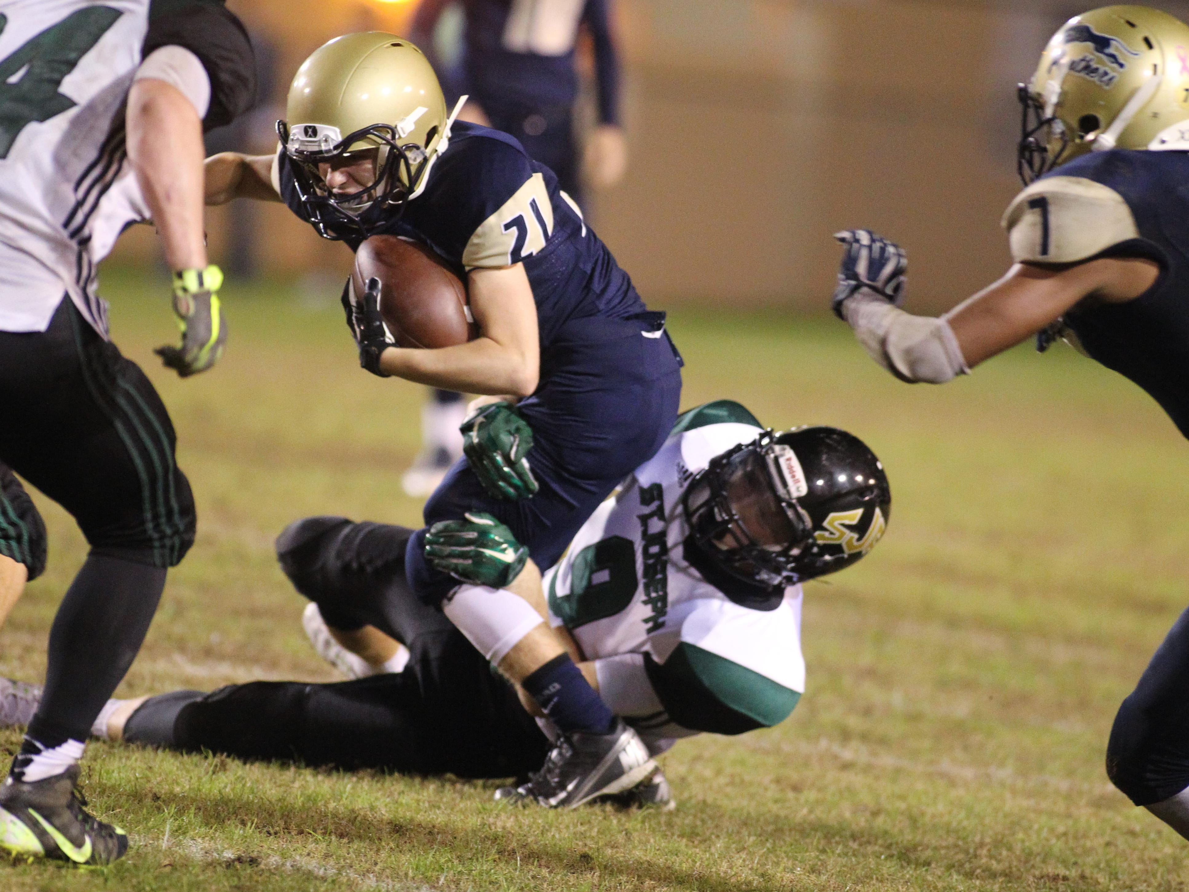 John Paul II's Aidan Murtha gets tackled by defenders in the championship game of the North Florida Football Conference at Gene Cox Stadium.