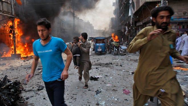 People flee the site of a blast in Peshawar, Pakistan, on Sunday.