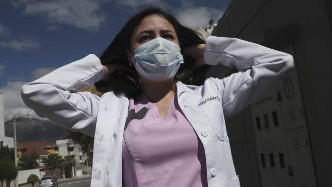 Dr. Maria Jose Casco adjusts her hair as she walks near her home in Quito, Ecuador, Wednesday, Aug. 5, 2020. Around the world, young people armed with new degrees, diplomas and professional qualifications are struggling to enter the workforce as the pandemic pushes the global economy into recession. Maria Jose Casco, a newly qualified doctor, hasn't found work after graduating in Ecuador in April. Casco, 24, said she's been searching for health-related jobs as well as work in other industries.