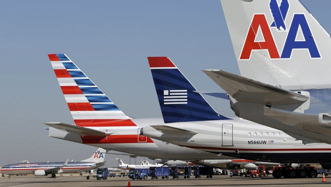 US Airways and American Airlines planes wait at the gates at Dallas/Fort Worth International Airport.