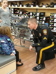"Cpl. Brandon Dunning, of the Smyrna Police Department, helps one of the kids involved with the ""Shop for a Cop"" program try on shoes at the Middletown Walmart."