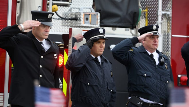 Firefighters salute Patrick Wolterman as a procession travels with his body through Woodlawn. An estimated 2,000 uniformed firefighters paid tribute to Wolterman, who died in the line of duty.