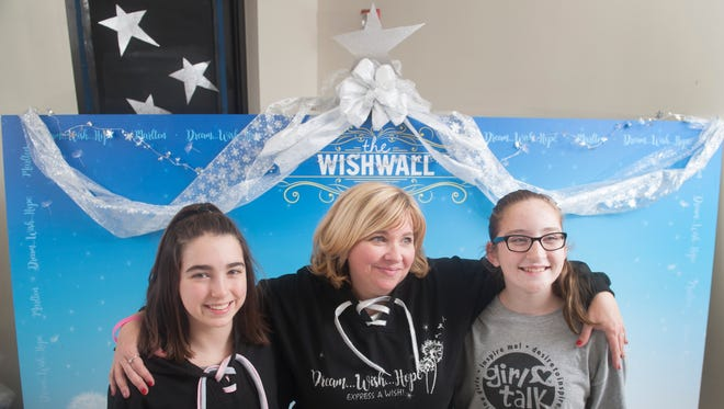 Founder and president of the Girl Talk Marlton chapter Mary Beth Iannarella, center, stands with Girl Talk members, 12-year-old Mia Mulholland of Marlton, left, and 12-year-old Emily Izzo of Marlton in front of the Wishwall that they and other members set up at the Evesham Township Library.  On Saturday, the Wishwall will be unveiled and dedicated in memory of singing star Christina Grimmie, a Marlton native who was killed last summer.