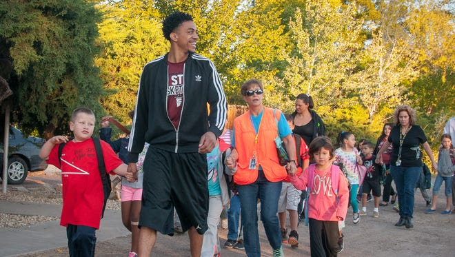 Mesilla Park Elementary first-grader Donald Fretwell, 7, and New Mexico State University sophomore Matt Taylor, a player on the NMSU basketball team, head a line of 98 students walking a half-mile from the Frank O'Brien Papen Center to the school Thursday morning.