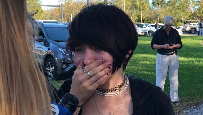A student reacts as she talks to a television reporter following a school shooting.