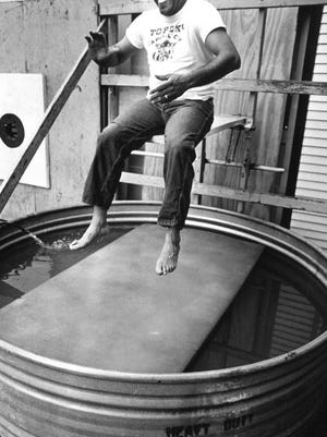 Jack Alexander, who won election as Topeka's first Black city commissioner in 1973, sits on a plank above the dunk tank at Topeka's annual Fiesta Mexicana in 1974.