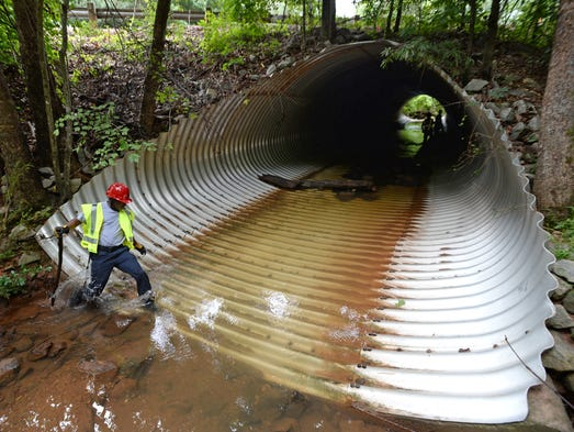 Greenville firefighters search Laurel Creek off Halton Road Monday, August 11, 2014 for Timothy Sullivan, who was swept into a drainage pipe near Haywood Mall Saturday night.