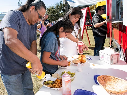 Brian Beyar, Axyria Beyar and Raquel Ramone-Beyar and condiments to their food during Food Truck Friday on Oct. 7, 2016, at Cannonsburgh Village.