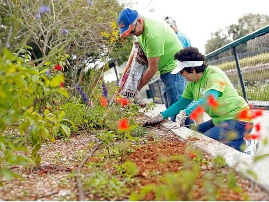 Volunteers Richard Brooks and Pat Graef clean up and spread mulch in Manatee Park's waterside butterfly garden.