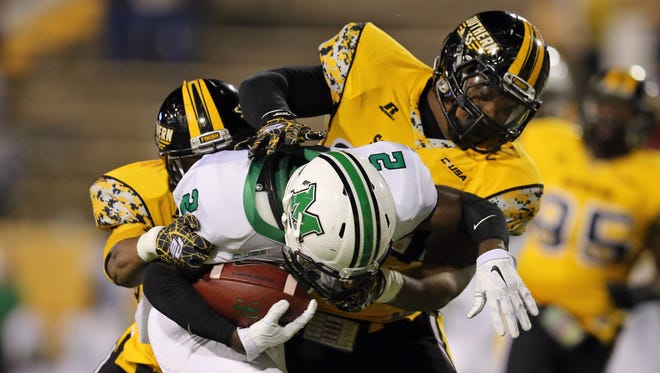 Southern Miss' Picasso Nelson Jr., left, and Dylan Bradley bring down a Marshall ball carrier during  a game last season.