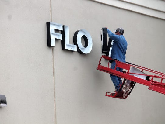 A crew member puts up outside signage on the newly