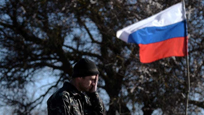 A member of pro-Russian forces stands guard at a checkpoint on the road from Simferopol to Sevastopol on Thursday as a Russian flag floats in the background.