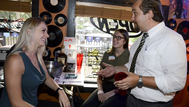 Bailey Scott, Carolyn Larock and Justin Anderson talk during an ENGAGE Young Professionals meeting on Oct. 12 at Bar Rescue in downtown Melbourne.
