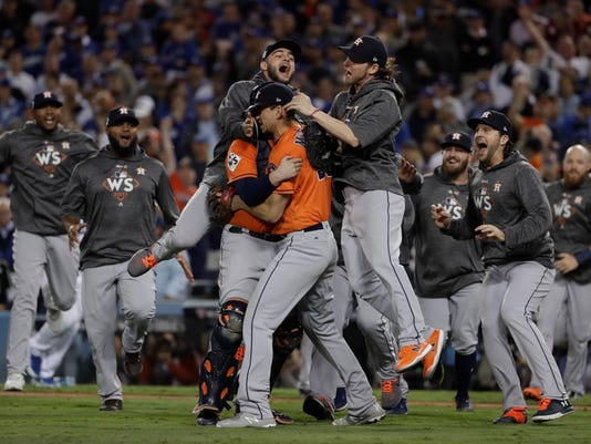 FILE - In this Nov. 1, 2017 file photo the Houston Astros celebrate after Game 7 of baseball's World Series against the Los Angeles Dodgers in Los Angeles. Rebuilding _ or, to use the less euphemistic term, tanking _ has become one of baseball's most polarizing topics in 2018. When the Astros won the World Series last season, four years after a 111-loss debacle, they became a shining example of how short-term pain can lead to long-term gain, but as other teams try to follow Houston's lead, they're being met with varying degrees of skepticism. (AP Photo/Matt Slocum, file)