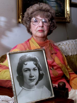 In this April 24, 2003, photo, Herlinda de la Vina holds a portrait of her niece, Irene Garza, the 25-year-old Texas schoolteacher and beauty queen in Edinburg, Texas, who was murdered in McAllen, Texas in 1960. The Maricopa County Sheriff's Department arrested 83-year-old John Feit, former priest, on Tuesday, Feb. 9, 2016, in the slaying of Garza.