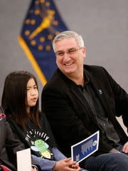 Gov. Eric Holcomb is seated next to Kayla Xu for before signing a bill to name the Say's Firefly as the Indiana state insect Friday, March 23, 2018, at Cumberland Elementary School in West Lafayette. Xu, who is now a fifth grade student at Happy Hollow Elementary, wrote a paper as a second grade student at Cumberland Elementary School about the lack of a state insect. The paper was the initiative behind Cumberland Elementary's push to make the Say's firefly the Indiana state insect.