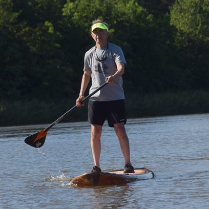 Wayne Denley stand up paddle boards on Buhlow Lake in Pineville. After shattering his heel, Denley researched online to find a sport where he could get a good workout that didn't included running