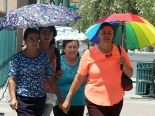 Gloria Cisneros, right, of Michoacan, Mexico, walks along the 300 block of San Antonio Street with a small group of visitors under the protection of umbrellas while visiting Downtown El Paso during triple-digit temperatures recently.