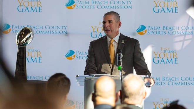 George Linley, Executive Director of the Palm Beach County Sports Commission speaks to the media about the impact of Super Bowl LIV in Palm Beach at a press conference at the Brightline station in downtown West Palm Beach on Monday, December 9, 2019. The Vince Lombardi trophy, which goes to the winning Super Bowl Team, sits on a pedestal to the left.