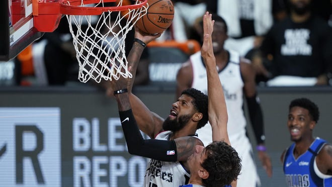 Los Angeles Clippers' Paul George drives to the basket against the Dallas Mavericks' Boban Marjanovic onTuesday in Lake Buena Vista, Fla.