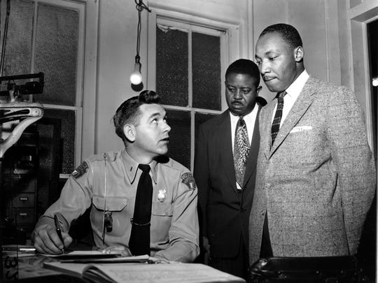 The Rev. Dr. Martin Luther King Jr., accompanied by The Rev. Ralph D. Abernathy, is booked by city police Lt. D.H. Lackey in Montgomery on Feb. 23, 1956. The civil rights leaders were arrested on indictments turned by the Grand Jury in the bus boycott.