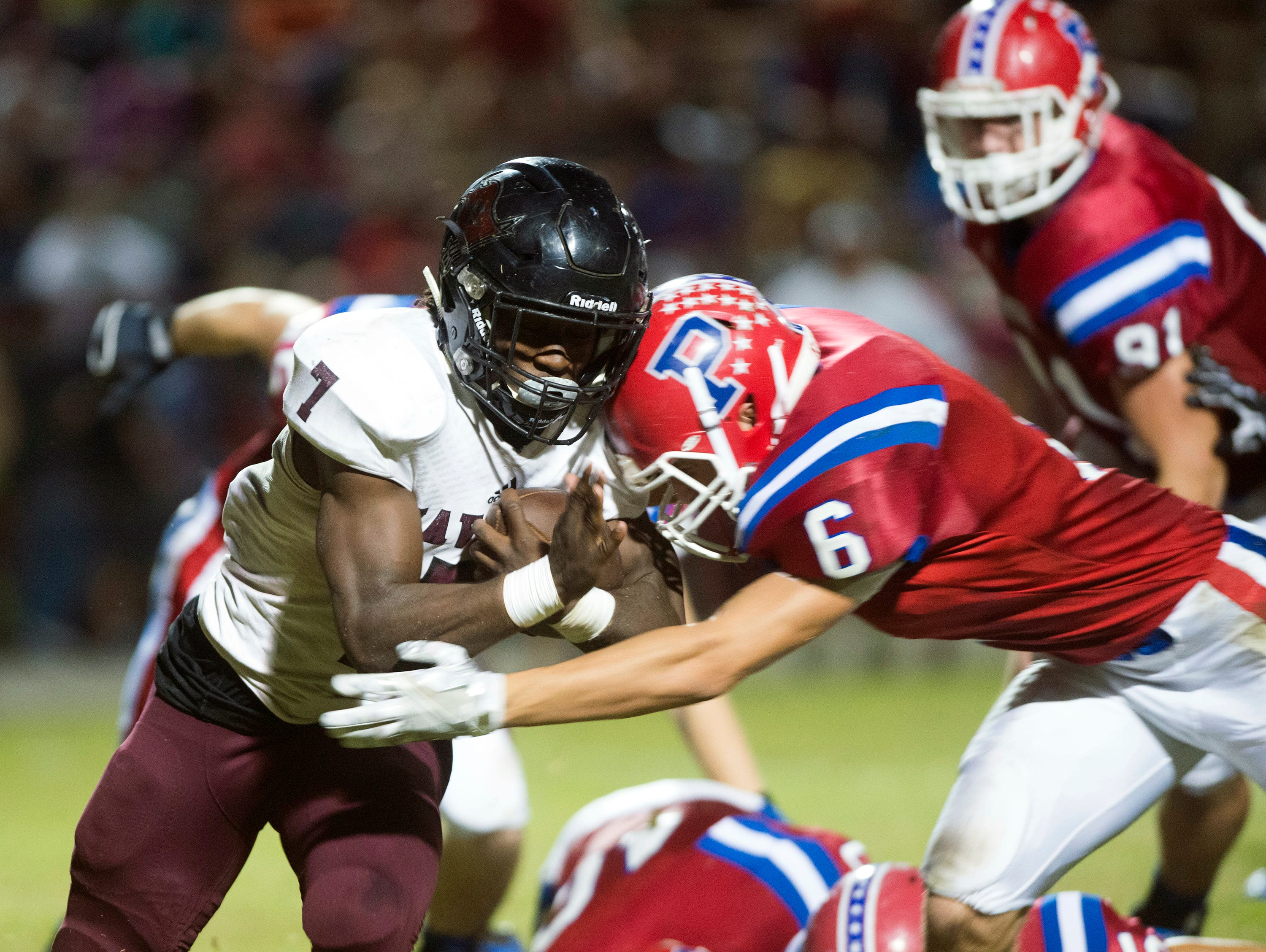 Navarre High School star running back Michael Carter (No. 7) gets wrapped up behind the line of scrimmage by the Pace High School line backer, Layne Plant, (No.6) during the District 2-6A matchup Friday night.