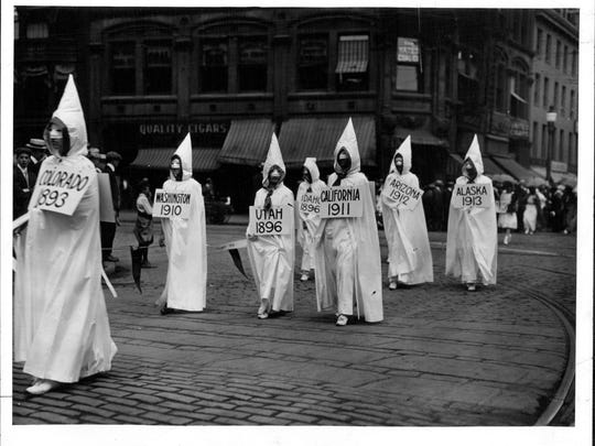 Masked Rochester Suffragettes march down Main Street to symbolize the states that which adopted equal vote amendments.
