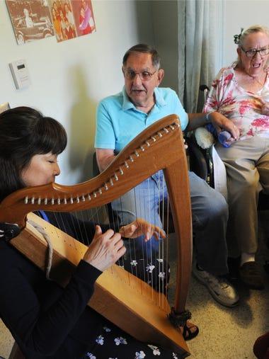 Therapeutic harpist Masayo Honjo plays for Bob Fassl