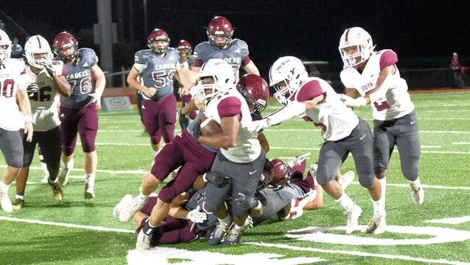 Desmond House keeps his legs moving and carries Cadet players trying to tackle him for eight or so yards for the first down early in the second quarter Friday night.