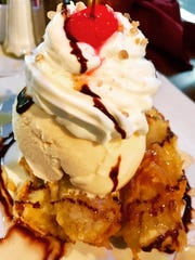 The fried banana ice cream dessert features fried bananas coated in a crispy oat crust and drizzled with honey and a crunchy topping.
