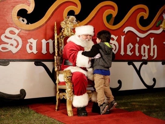 A men dressed as Santa Claus greets 3-year-old Max