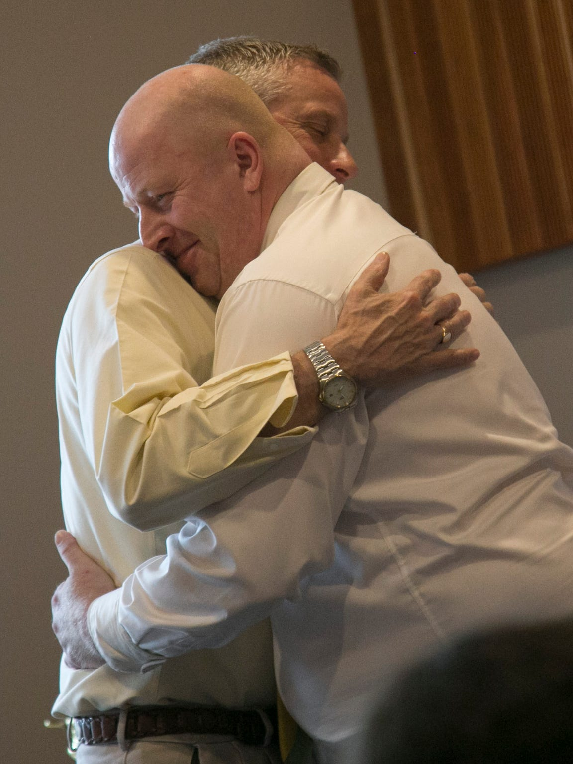 Jerome Kurtz hugs Dan Gates after giving testimonial