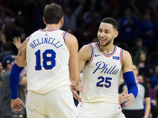 Philadelphia 76ers' Ben Simmons, right, of Australia, reacts to his assist on a three-point basket by Marco Belinelli, left, of Italy, during the first half of an NBA basketball game against the Cleveland Cavaliers, Friday, April 6, 2018, in Philadelphia. (AP Photo/Chris Szagola)