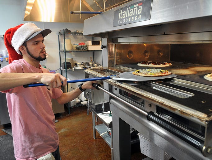 Josh Holcomb pulls a fresh pizza from an Italian-made